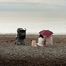 A young couple sitting under an umbrella on a deserted beach on a typically british wet summer afternoon with a child´s buggy next to them  Wales UK