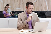 Germany, Cologne, Business man in cafe using laptop