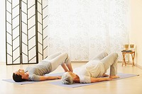 Two women arching back on gym mat