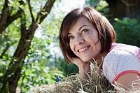Germany, Bavaria, Woman lying in hay, smiling, portrait