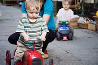 Germany, Berlin, Mother and boy 2_3 3_4 on toy tractor, close_up