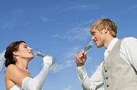 Germany, Bavaria, Bridal couple drinking champagne outdoors, side view, portrait