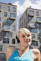 Germany, Berlin, Young woman listening to MP3_Player, portrait