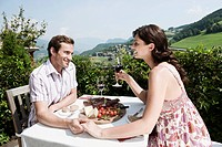Italy, South Tyrol, Seiseralm, Couple in restaurant holding hands, smiling, portrait