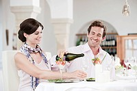 Couple in restaurant, man pouring wine into glass, smiling, portrait