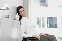 Germany, Cologne, Business woman sitting in office, side view, portrait