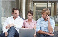 Germany, Cologne, Three business people sitting side by side, using laptop