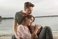 Germany, Berlin, Lake Wannsee, Young couple sitting by lake