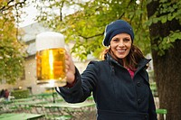 Germany, Bavaria, Munich, English Garden, Woman in beer garden holding beer mug, smiling, portrait