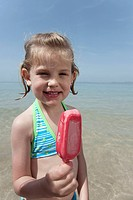 Spain, Mallorca, Girl 4_5 eating icecream on beach, portrait
