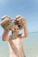 Spain, Mallorca, Boy 8_9 with sandy hands playing at the beach