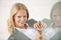 Businesswoman smiling, reflection in glass pane