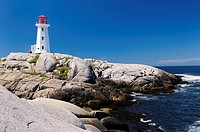 Peggys Cove Nova Scotia lighthouse on smooth granite rocks with accordian player and surf