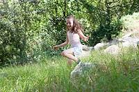 Girl skipping through grass