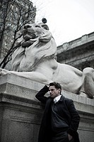 Man by lion statue at new york public library