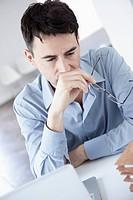 Businessman in office, musing, portrait
