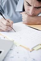 Businessman in office writing, portrait