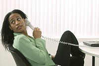 African American Woman Looking Over Her Shoulder While Talking On The Telephone At Work
