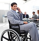 Businessman in a wheelchair on phone during a meeting with his colleagues