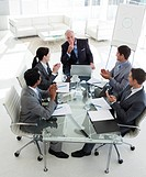 Young business people clapping their senior manager at the end of a meeting
