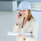 Young female engineer on phone carrying blueprints