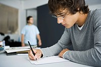 College student writing at desk in classroom