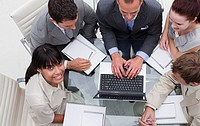 High angle of smiling ethnic businesswoman working with her team in a meeting