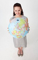 High angle of a young businesswoman holding the Earth planet