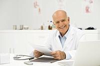 Doctor at desk smiling at camera, portrait