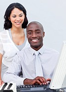 Smiling businesswoman and her colleague working at a computer in the office
