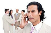 Serious businessman talking on phone against a white background