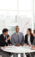 Afro_american manager in a meeting with his team smiling at the camera