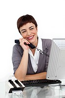 Joyful Businesswoman holding a telephone at her desk against a white background