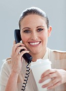 Caucasian businesswoman on phone drinking a coffee at her desk