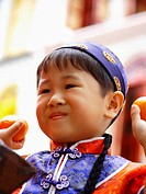 Close_up of a boy holding oranges and smiling