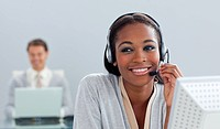 Radiant businesswoman using headset at her desk in the office
