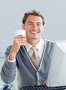 Young businessman drinking a coffe at his desk in the office