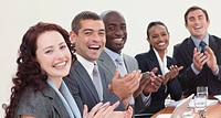 Happy businessteam laughing and clapping in a meeting