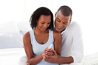 Happy couple finding out results of a pregnancy test in the bedroom