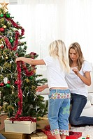 Blond little girl and her mother decorating Christmas tree at home