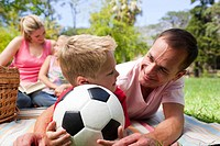 Father and son holding a soccer ball with their family reading in the background at a picnic