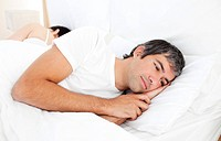 Upset man lying in his bed separately from his wife