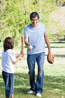 Adorable little boy playing baseball with his father in the park