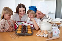 Merry family presenting their muffins in the kitchen