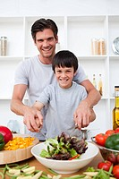 Portrait of a happy father cooking with his son in the kitchen