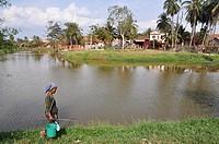 Siem Reap (Cambodia): a woman walking along the Siem Reap river´s bank
