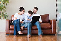 Parents and son playing together with a laptop on a couch