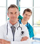 Smiling young doctor in focus in a line with his colleagues