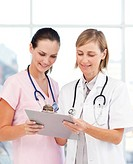 Portrait of a nurse and doctor reading a medical report