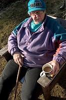 An elderly woman sitting outdoors